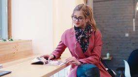Entzückende junge Frau in einem stilvollen Blick, der im café sitzt, die Zeitschriftenseiten leicht schlägt und Musik mit hört stock footage