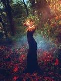 Entzückende junge Hexe wirft einen Bann im Wald Stockfotos