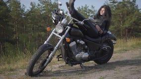 Entzückende junge kaukasische Frau in einer schwarzen Lederjacke und in Hosen, die auf einem klassischen Motorrad liegen Hobby, r stock video