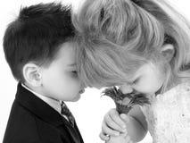 Entzückende junge Kinder, die zusammen Gänseblümchen riechen Lizenzfreie Stockfotos