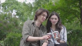 Entzückende junge nette Paare des Porträts in der zufälligen Kleidung, die zusammen Zeit im Park, Datum habend verbringt Die Stud stock video footage
