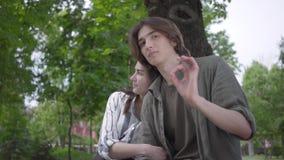 Entz?ckende junge Paare des Portr?ts in der zuf?lligen Kleidung, die zusammen Zeit im Park, ein Datum habend verbringt Liebhaber, stock video