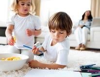 Entzückende Kinder, die Chips und das Zeichnen essen lizenzfreies stockbild