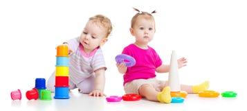 Entzückende Kinder, die mit bunten Türmen spielen stockbild