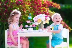 Entzückende Kinder, die Spaß an der Gartenteeparty haben Lizenzfreies Stockfoto