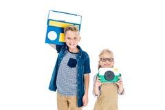 entzückende Kinder mit Kamera und Tonbandgerät, das an der Kamera lächelt Lizenzfreie Stockfotos