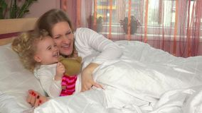 Entzückende Kinderlüge im Bett nahe ihrer liebevollen glücklichen Mutterfrau stock video