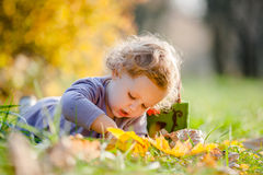 Entzückende kleine blonde Mädchenlügen lizenzfreies stockfoto