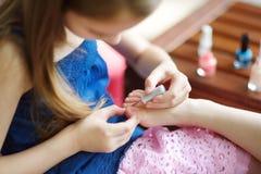 Entzückende kleine Mädchen, die den Spaß zu Hause spielt mit dem bunten Nagellack tut Maniküre und malt Nägel haben stockfotografie