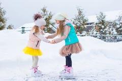 Entzückende kleine Mädchen, die draußen auf Eisbahn eislaufen Stockfoto