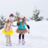 Entzückende kleine Mädchen, die draußen auf Eisbahn eislaufen Lizenzfreie Stockfotos