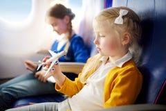 Entzückende kleine Mädchen, die durch ein Flugzeug reisen Kinder, die durch Flugzeugfenster sitzen und mit Spielzeugfläche spiele lizenzfreies stockfoto