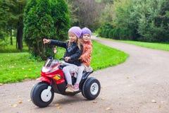 Entzückende kleine Mädchen, die herein auf das motobike des Kindes fahren Stockbild