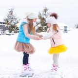 Entzückende kleine Mädchen, die herein auf Eisbahn eislaufen Stockfotos