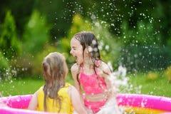 Entzückende kleine Mädchen, die im aufblasbaren Babypool spielen Die glücklichen Kinder, die im bunten Garten spritzen, spielen M Lizenzfreies Stockfoto