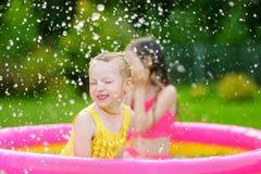 Entzückende kleine Mädchen, die im aufblasbaren Babypool spielen Die glücklichen Kinder, die im bunten Garten spritzen, spielen M Lizenzfreies Stockbild