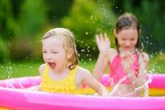 Entzückende kleine Mädchen, die im aufblasbaren Babypool spielen Die glücklichen Kinder, die im bunten Garten spritzen, spielen M Lizenzfreie Stockbilder