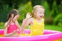 Entzückende kleine Mädchen, die im aufblasbaren Babypool spielen Die glücklichen Kinder, die im bunten Garten spritzen, spielen M Stockbild
