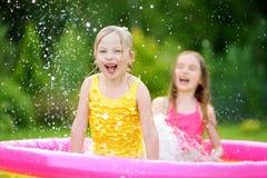 Entzückende kleine Mädchen, die im aufblasbaren Babypool spielen Die glücklichen Kinder, die im bunten Garten spritzen, spielen M Stockfotos