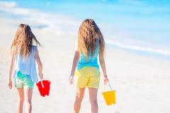 Entzückende kleine Mädchen, die mit Sand auf dem Strand spielen Hintere Ansicht von den Kindern, die entlang den Strand gehen Lizenzfreie Stockfotos