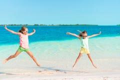 Entzückende kleine Mädchen, die Spaß auf dem Strand voll von Starfish auf dem Sand haben Stockbilder