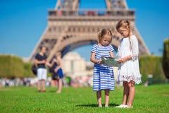 Entzückende kleine Mädchen mit Karte von Paris-Hintergrund der Eiffelturm Lizenzfreies Stockbild