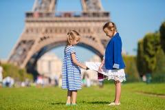 Entzückende kleine Mädchen mit Karte von Paris-Hintergrund der Eiffelturm Lizenzfreie Stockfotografie