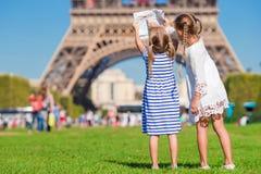 Entzückende kleine Mädchen mit Karte von Paris-Hintergrund der Eiffelturm Lizenzfreie Stockbilder
