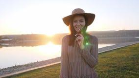 Entzückende lächelnde Aufstellung des jungen Mädchens an der Kamera während des Gehens nahe dem See stock video