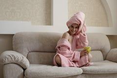 Entzückende lächelnde Frau, die auf gemütlicher Couch sich entspannt Stockfotos