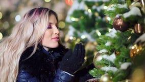 Entzückende lächelnde Frau, die den Schlag auf Schneeflocken nahe dem Überraschen des verzierten Weihnachtsbaums genießt stock video