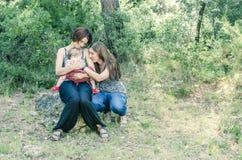 Entzückende lesbische Paare mit ihrem Baby in der Natur Stockbild
