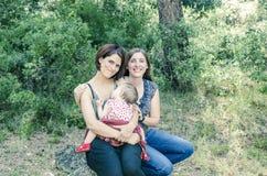 Entzückende lesbische Paare mit ihrem Baby in der Natur Stockfotos