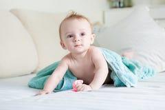 Entzückende 9 Monate alte Baby bedeckt im blauen Tuch, das auf Bett kriecht Lizenzfreie Stockfotografie