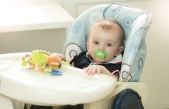 Entzückende 9 Monate alte Baby mit dem soother, das im Stuhl an sitzt Stockfoto
