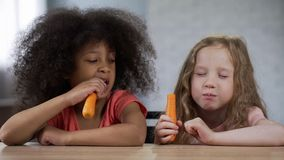Entzückende multiethnische Mädchen, die bei Tisch sitzen und Karotten, gesunde Imbisse essen lizenzfreie stockbilder