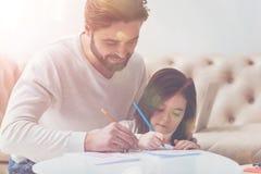 Entzückende nette Familie, die zusammen zeichnet Stockbilder
