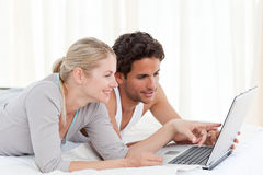 Entzückende Paare, die ihren Laptop auf dem Bett betrachten stockfotografie