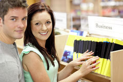 Entzückende Paare, die nach einem Geschäftsbuch suchen Lizenzfreie Stockfotografie