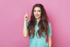 Entzückende schöne junge Frau mit dem langen Haar erhält gute Idee in Verstand angehobenem Zeigefinger auf lokalisiertem rosa Hin Stockfotos