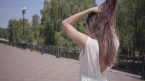 Entzückende tragende Sonnenbrille des jungen Mädchens und langes weißes ein Sommermodekleid, das draußen geht Freizeit einer hübs stock footage