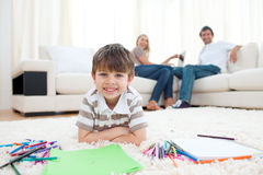 Entzückende Zeichnung des kleinen Jungen, die auf dem Fußboden liegt Lizenzfreies Stockfoto