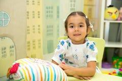 Entzückender Asiat, kasachisches Kindermädchen im Kindertagesstättenraum Kind im Kindergarten in der Montessori-Vorschule- Klasse Stockbild