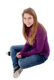 Entzückender blonder Jugendlicher, der die Kamera sitzt auf Boden betrachtet Stockfoto