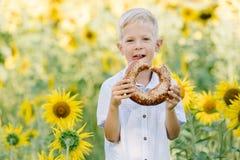 Entzückender blonder Junge, der draußen Bagel auf Sommersonnenblumenfeld isst Stockfoto