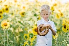 Entzückender blonder Junge mit Bagel auf Sommersonnenblumenfeld draußen Lizenzfreie Stockfotos