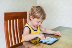 Entzückender blonder Kleinkindjunge, der mit einer digitalen Tablette spielt Stockfotos
