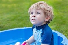 Entzückender blonder Kleinkindjunge, der mit Wasser, draußen spielt Lizenzfreies Stockbild