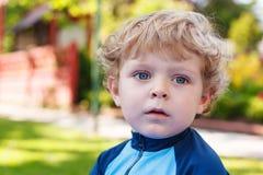 Entzückender blonder Kleinkindjunge, der mit Wasser, draußen spielt Lizenzfreie Stockfotografie