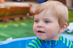 Entzückender blonder Kleinkindjunge, der mit Wasser, draußen spielt Lizenzfreies Stockfoto